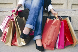 image of the legs only of a woman wearing jeans with shopping bags on either side