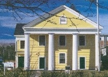 image of an historic house with yellow wood clapboards and white trim including columns