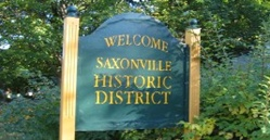 "image of the ""welcome to historic saxonville sign"" - green wooden sign with gold carved letter"