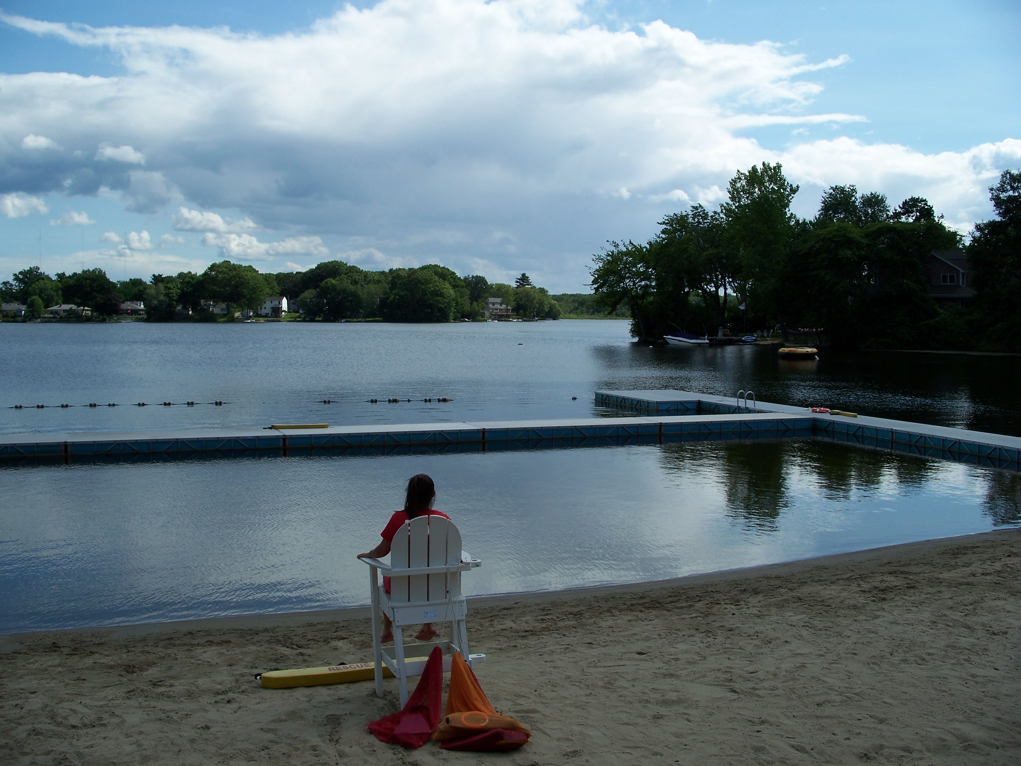 image of a lifeguard on a chair on a small beach facing a calm lake with trees in the background