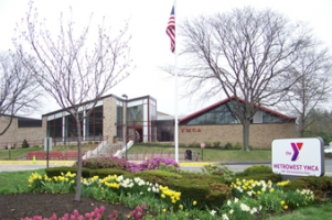 image of the front of the MetroWest YMCA - light brick building with a peaked roof and glass facade