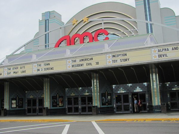 Image of the entry to the AMC Framingham movie theater - rounded archway with lighted AMC letters