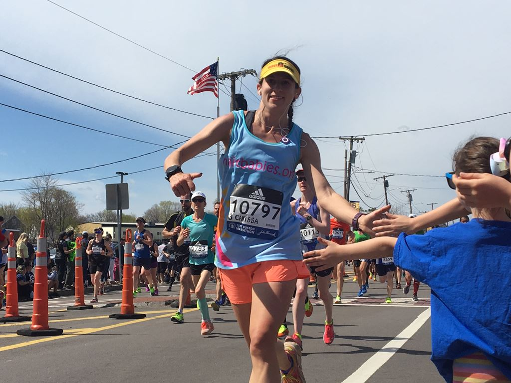 Female runner with a blue shirt and yellow visor gives kids high fives at the 6 mile moment