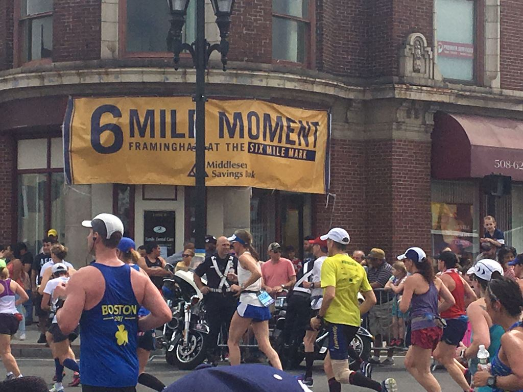 image of 6 mile moment banner on an historic brick building with runners and police in front