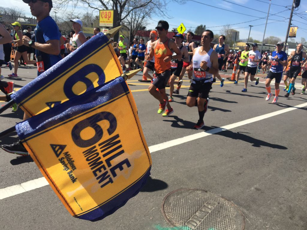 image of two 6 mile moment flags with runners in the background