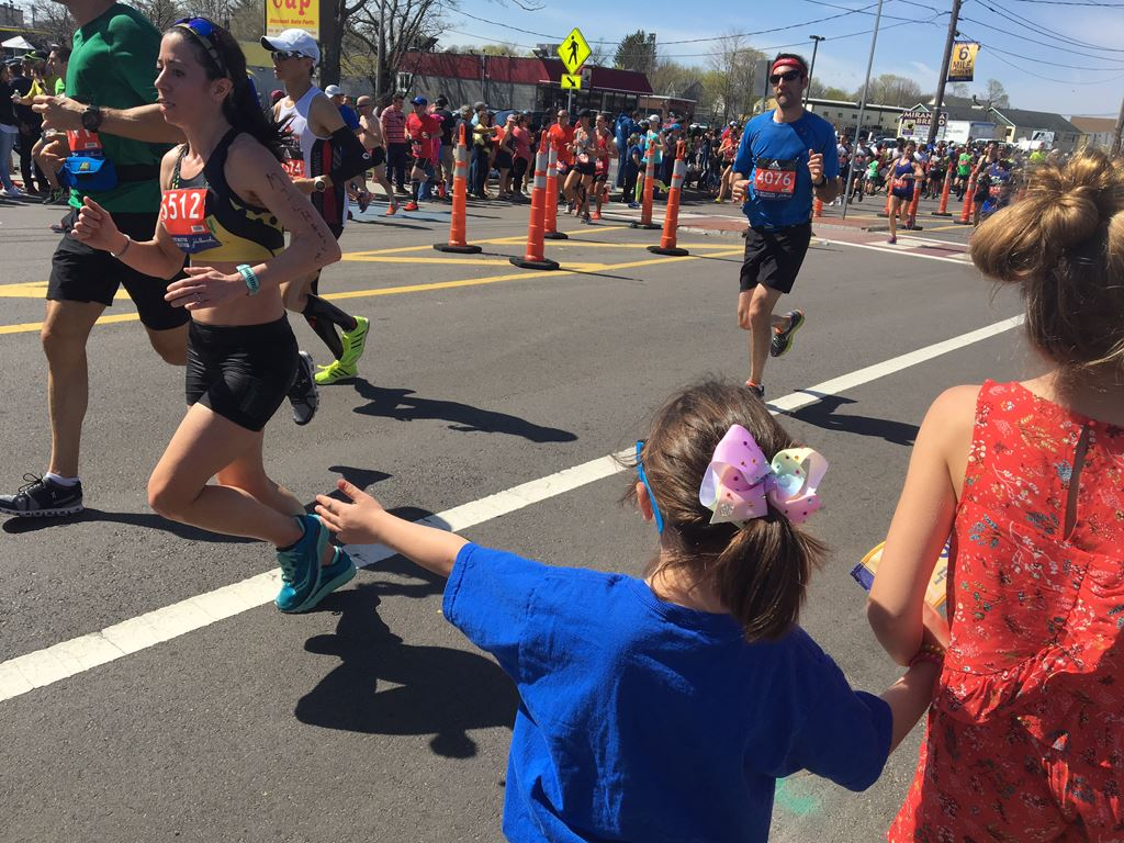 image of a girl with a bow and a blue shirt holding out her hand for runners to high five