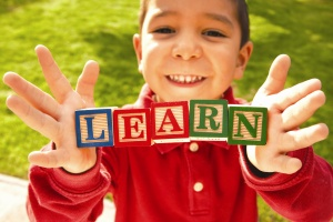 view of a boy holding blocks that spell out the word LEARN
