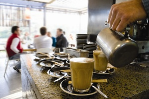 close up image of a cappucino in a mug on a coffee bar with patrons in the background