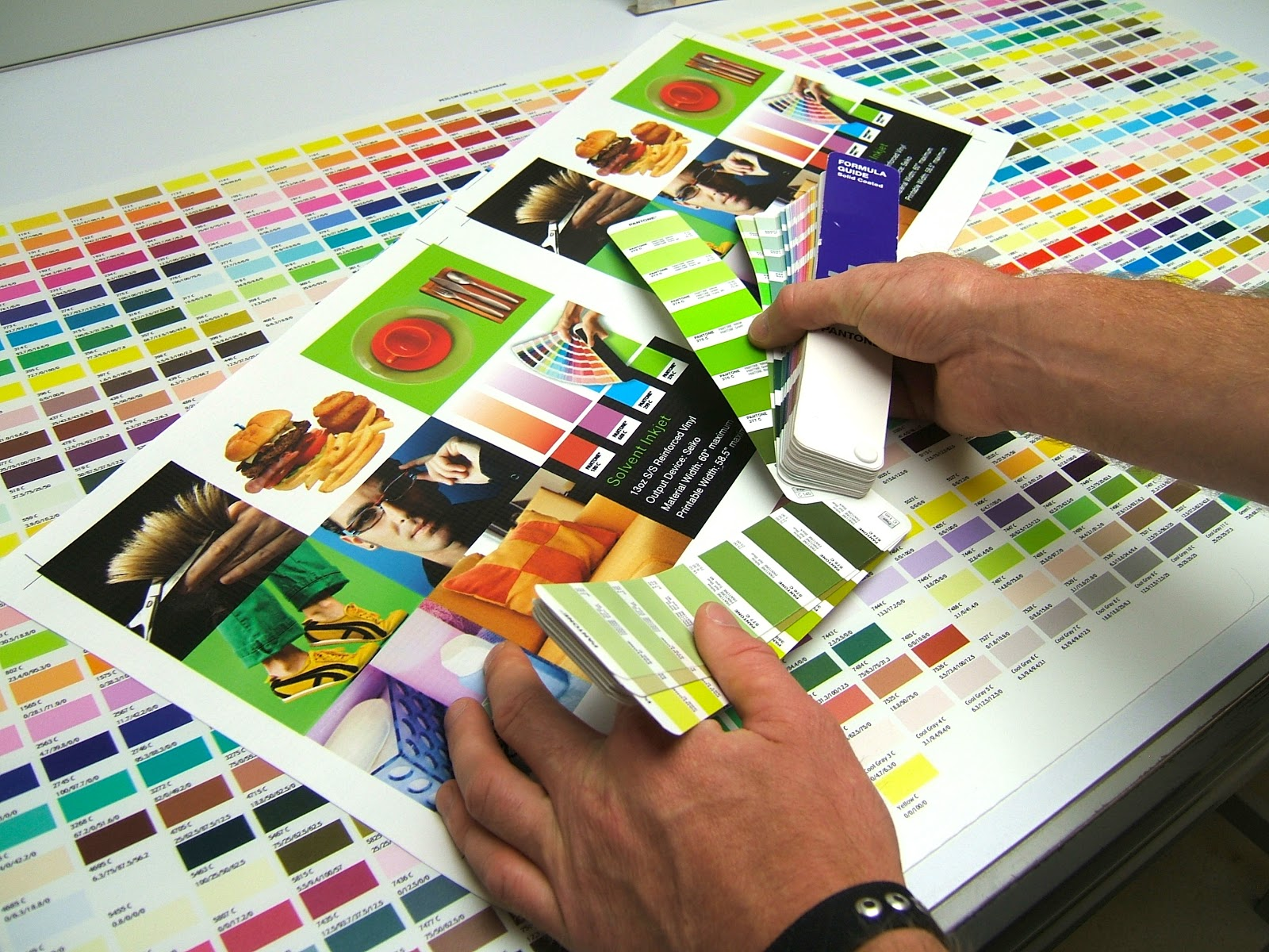 colorful image of hands holding a graphic layout surrounded by color swatches
