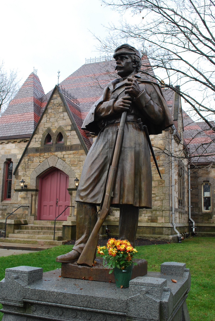 view of a statue of a soldier with an historic building made of large stones with a red roof behind