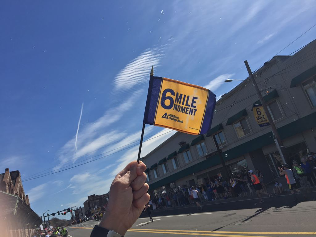 Image of the 6 Mile Moment flag with the blue sky behind and a building in the background