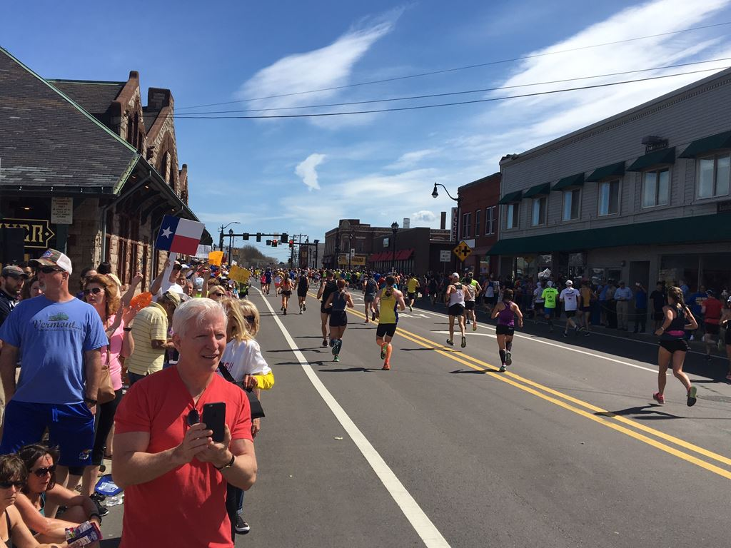 wide angle view of runners at the 6 mile moment in Framingham with historic depot on the left and co