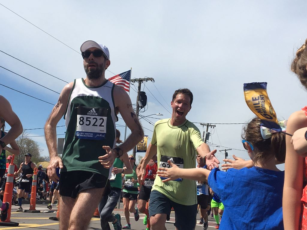 view of happy male runner giving a girl with a bow a high five