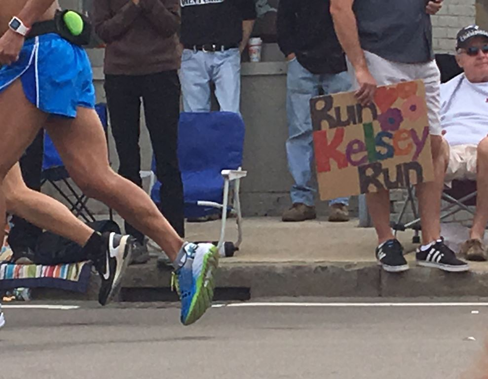 "man holding a home made sign on cardboard that says ""Run Kelsey Run"" with flowers"