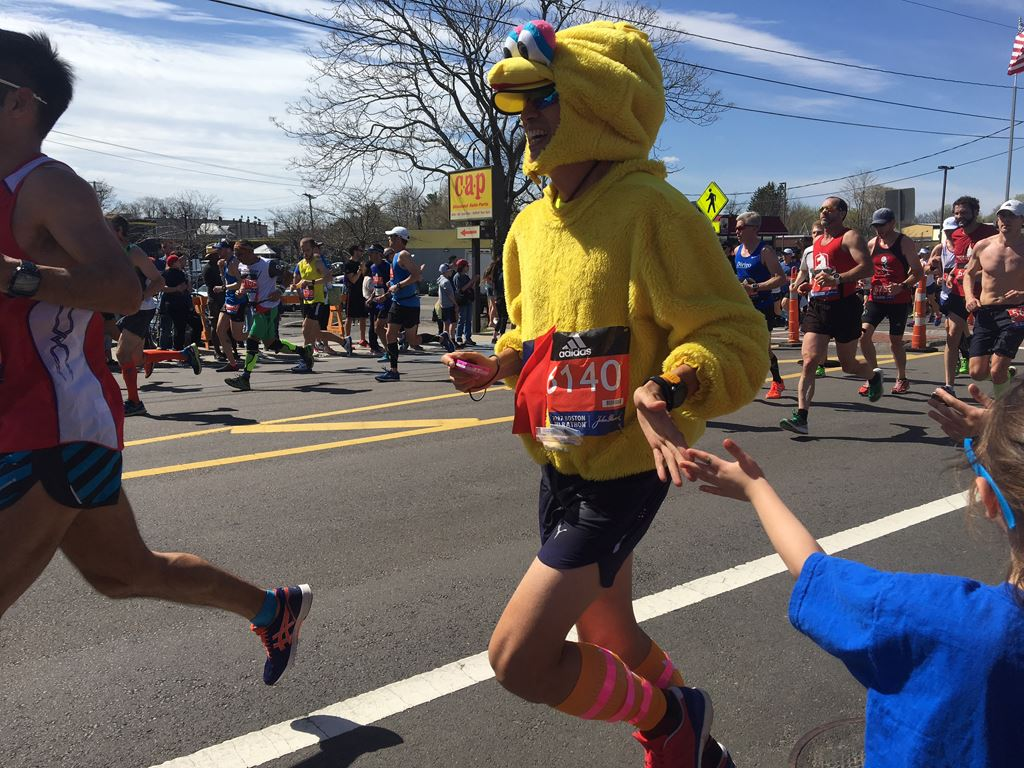 male runner in a chicken costume gives a child a high five